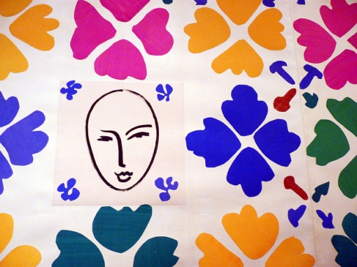 Large piece of contemporary art with stylized images of flowers and a line drawing of a face.