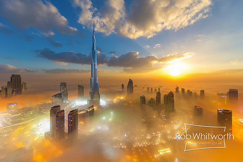 High sky view of fluffy clouds, brilliontly colors fog around buildings at dusk in Dubai.