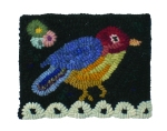 A small piece of art  featuring a bird rug hooked by Nancy Smith.