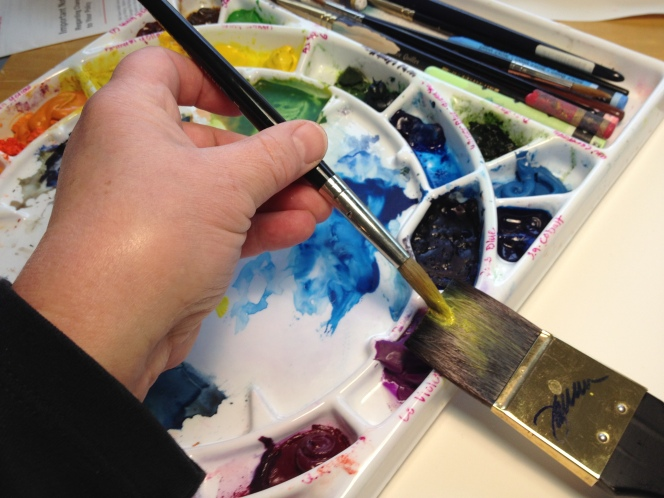 A photo of the left hand of the artist holding a brush as she applies paint to the bristles of a flat brush.