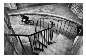A bicyclist is riding along a street at the bottom of a windy staircase.