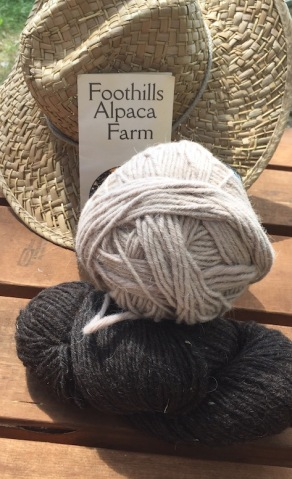 A skein of charcoal colored yarn, a ball of cream-colord yard, and a straw hat.